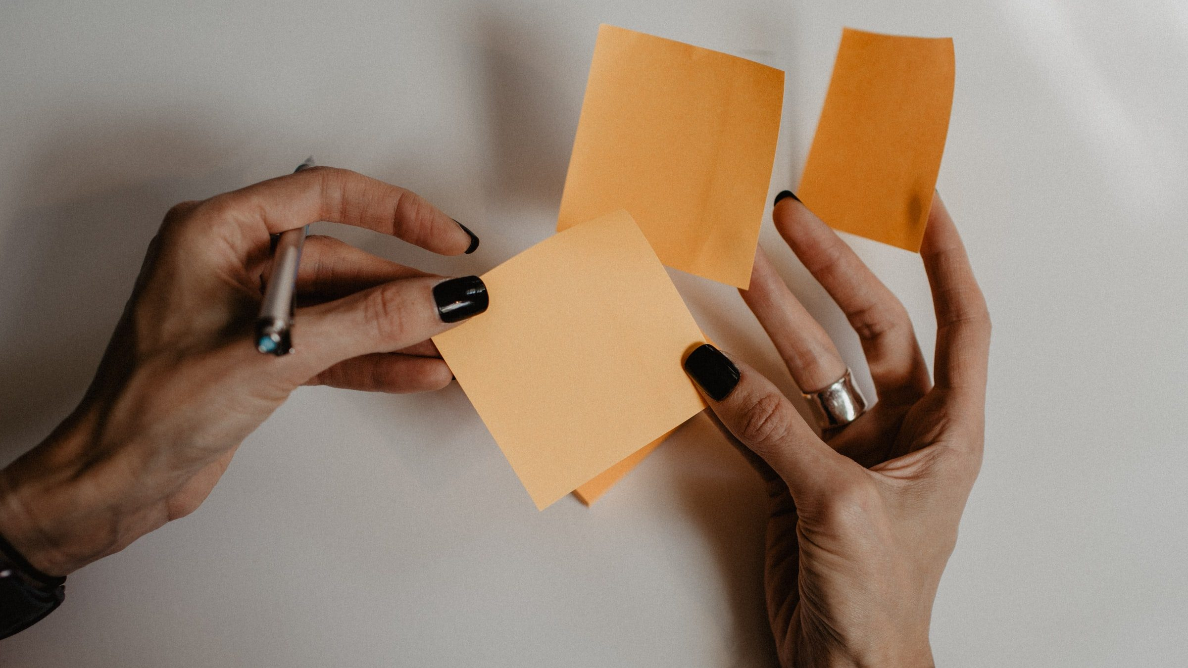 A pair of hands holding a set of sticky notes and a pen