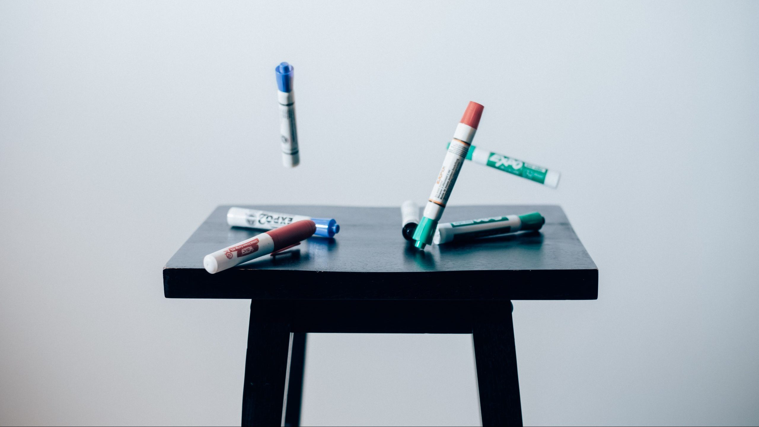 A black stool with dry erase markers mid-air above it