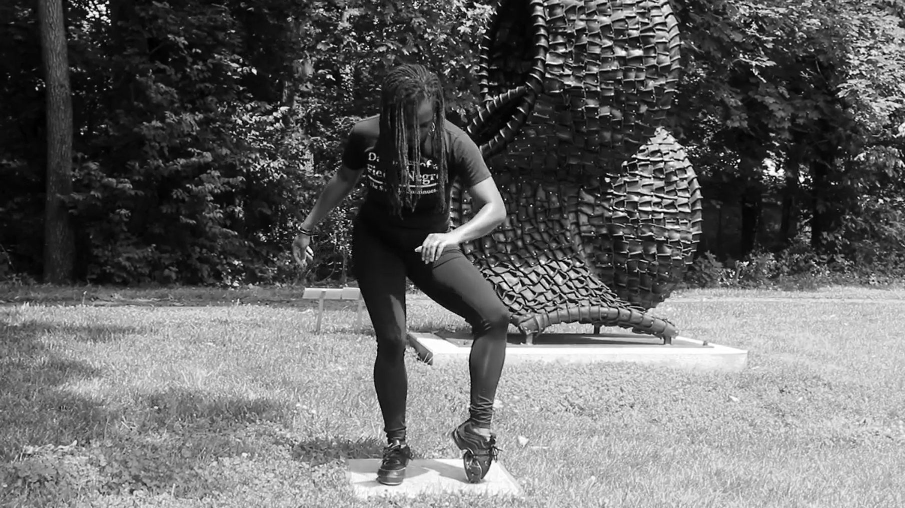 A person bent over in a dance move in front of a black undulating sculpture in an outdoor setting
