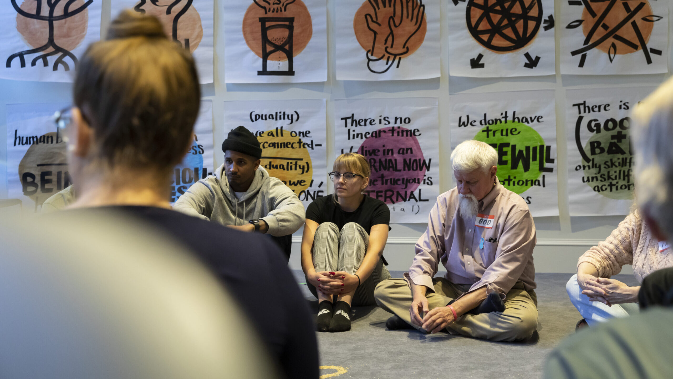 A group of people seated in a circle on the floor in front of drawings hanging on a gallery wall
