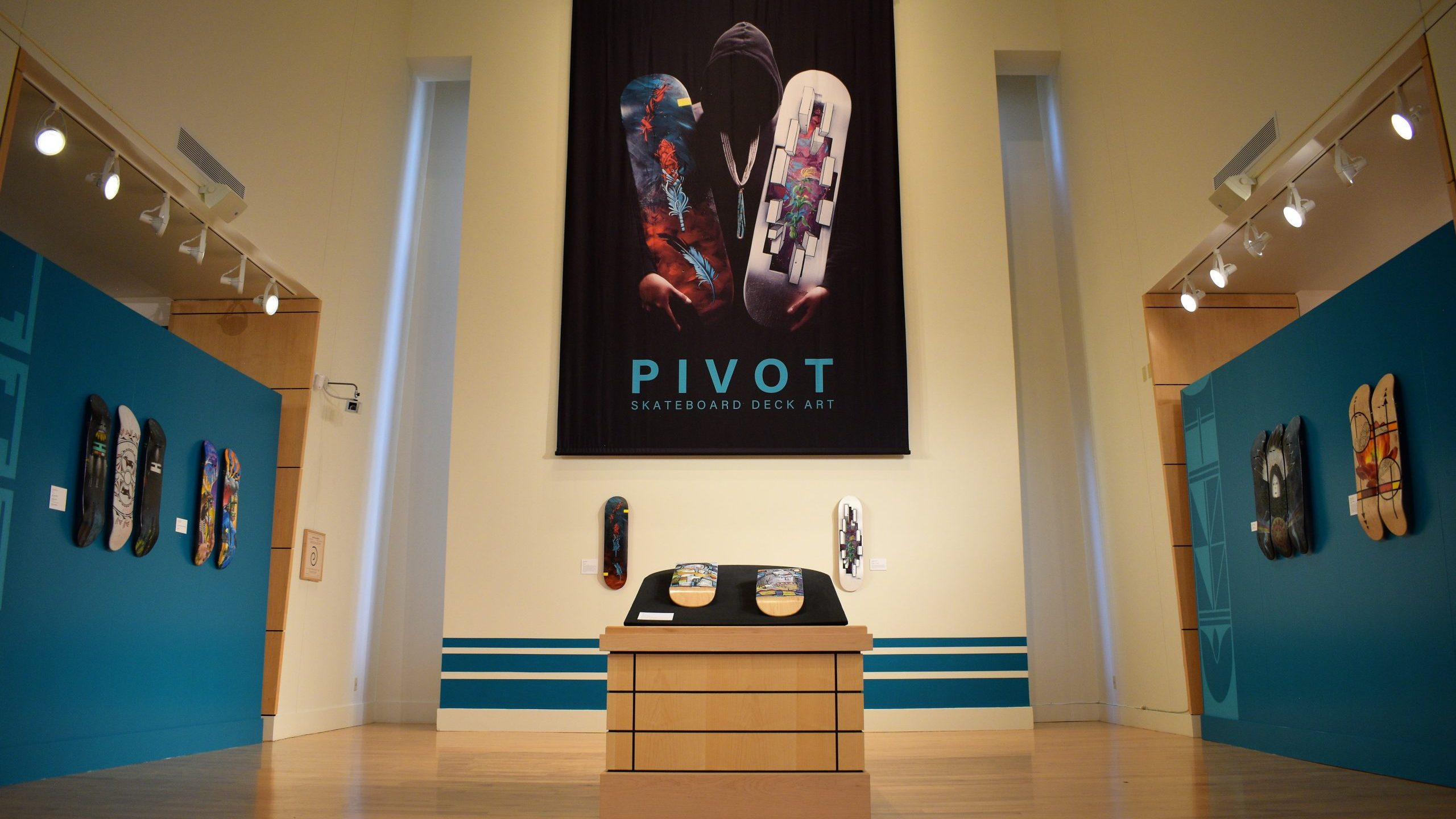 """An exhibition gallery with skateboard decks and the title """"PIVOT"""""""