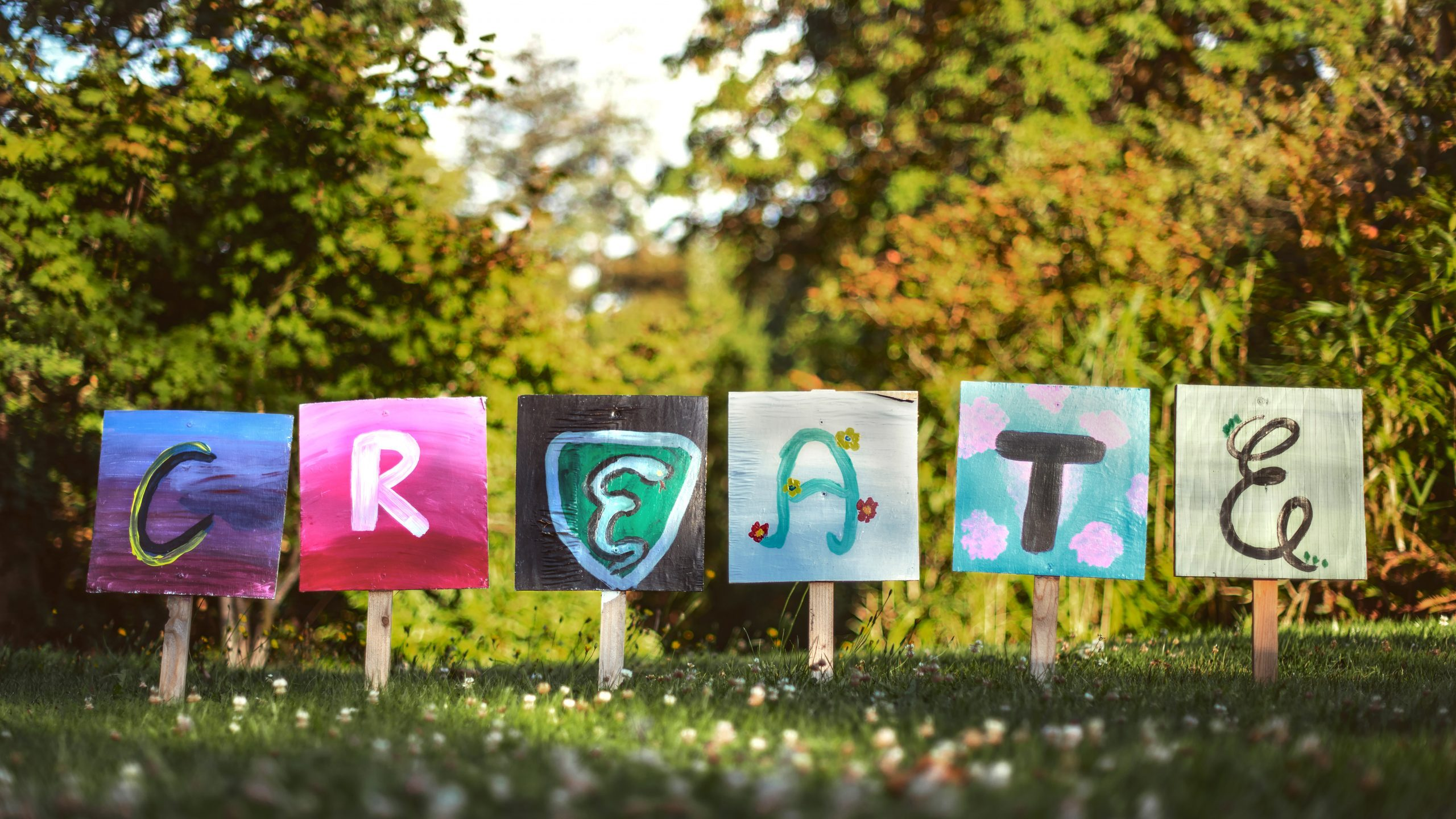 """A line-up of hand-drawn signs on a lawn spelling out """"Create"""""""
