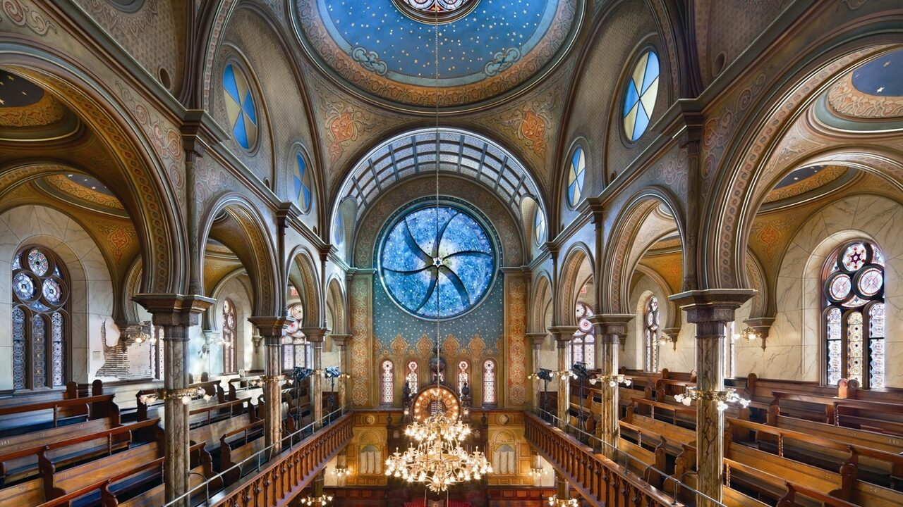 Interior view of a historic synagogue with round stained-glass windows