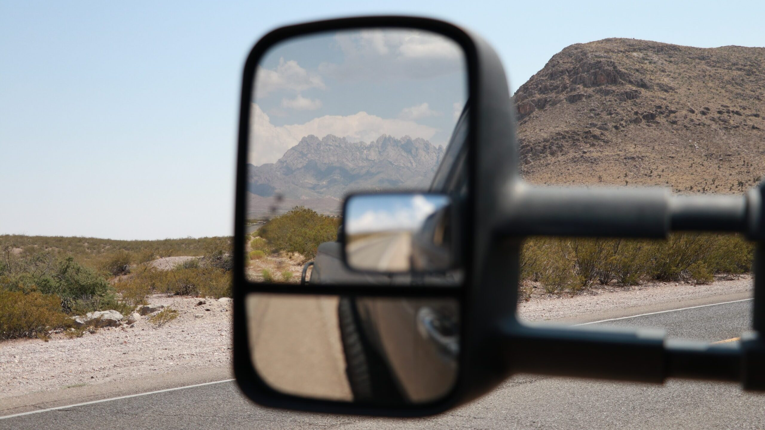 A rearview mirror of a vehicle in the desert