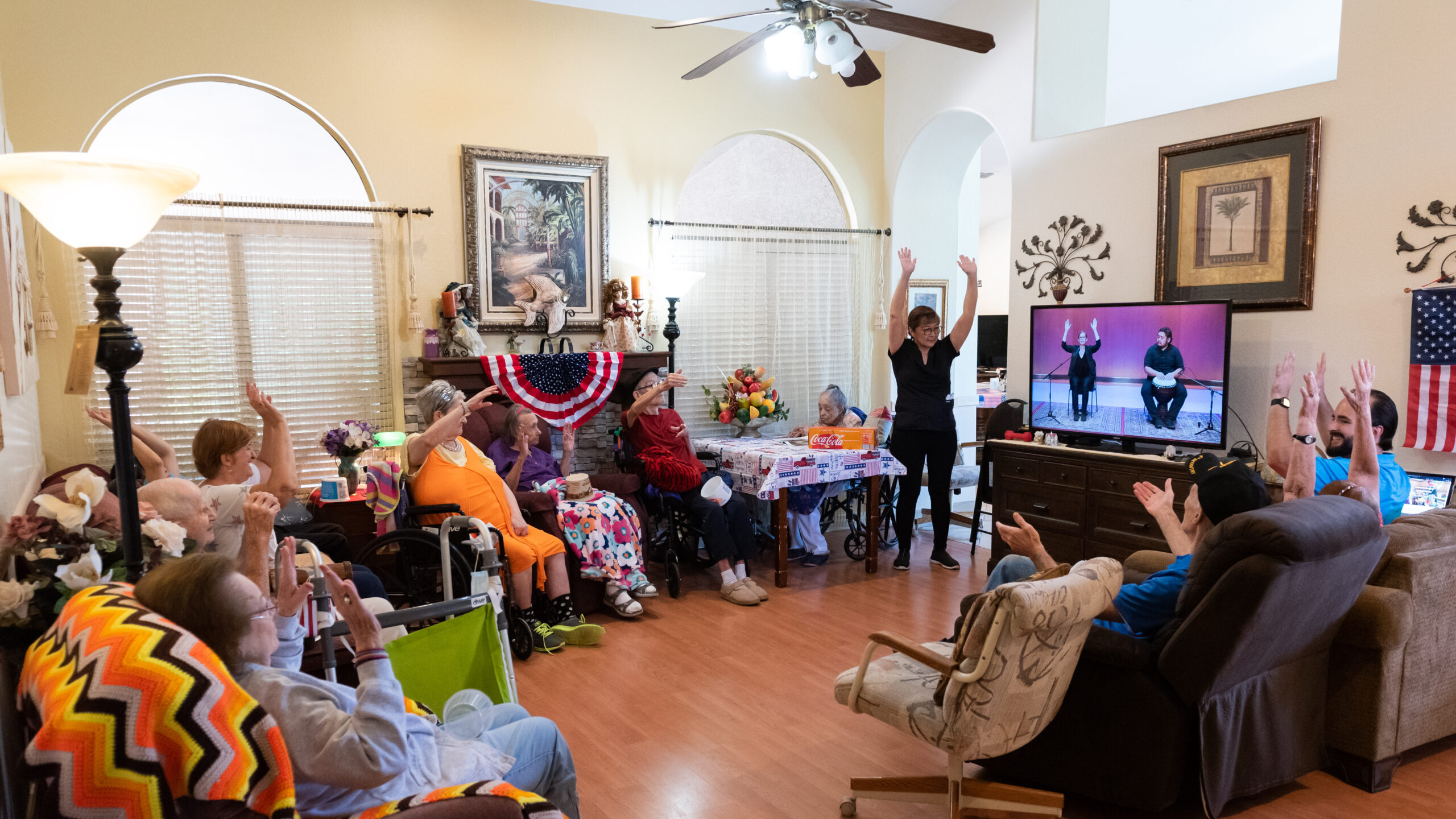 A group of seniors and senior care staff seated around a television showing a video of a drummer and instructor