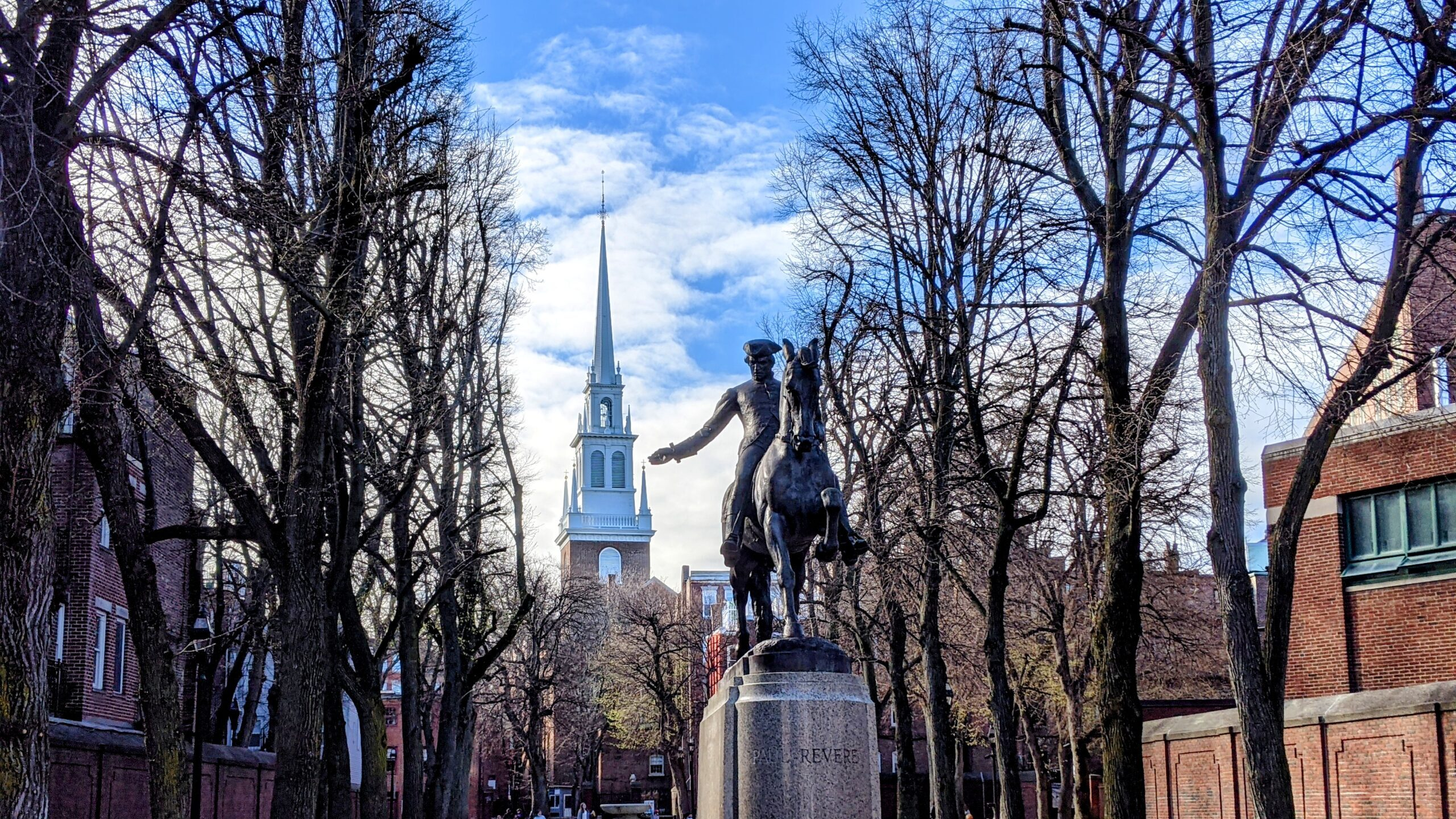 A public square with a state of Paul Revere and the steeple of a church visible in the background.